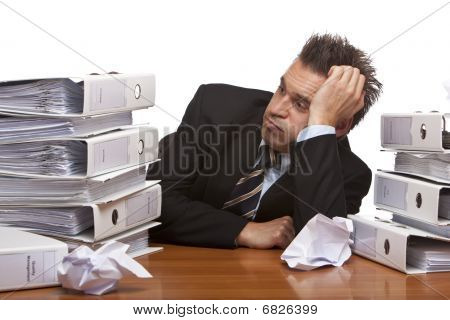 Stressed Business Man Sitting Frustrated Between Folder Stacks In Office