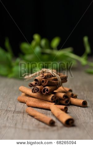 Pile Of Cinnamon Sticks On Top Of Wooden Table Before Fresh Basilica With Black Bacground.