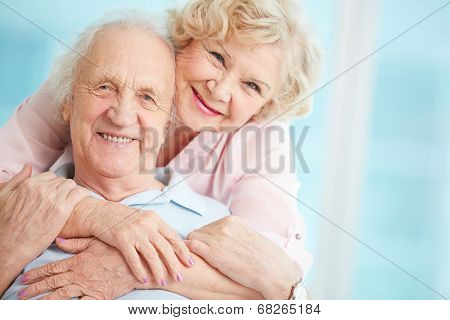 Happy and affectionate elderly couple posing for camera