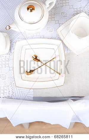 Composition with teapot, saucer and spoons on wooden table background