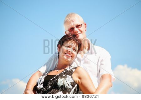 Mature couple on blue sky background
