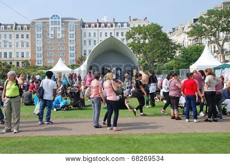 ST.LEONARDS-ON-SEA, ENGLAND - JULY 12, 2014: The audience sit on the grass at the annual St.Leonards Festival. The free music and entertainment community event was first held in 2006.