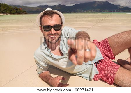 smiling young man lying down on the beach and points finger to the camera