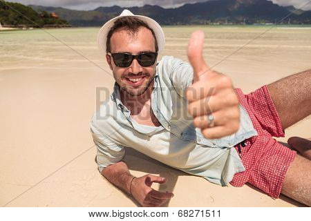 happy young man with hat and sunglasses lying down on the beach of seychelles and makes the ok thumbs up hand sign