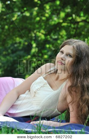 Young Woman Daydreaming In Park
