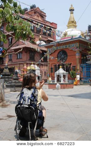 Tourist With Camera In Front Of Budhist Monastery