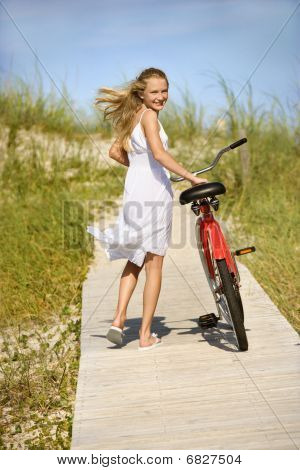 Girl Walking Bike On Boardwalk.