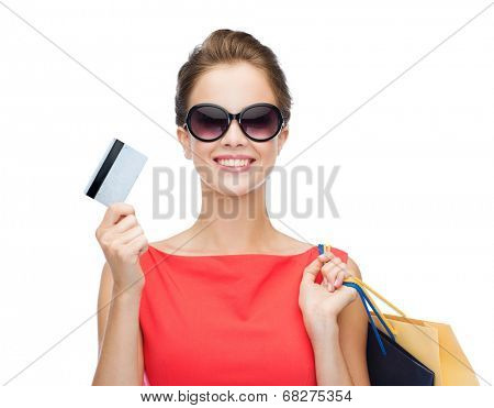 shopping, sale, christmas and holiday concept - smiling elegant woman in red dress with shopping bags and plastic card
