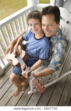 Father And Son On Porch Playing Guitar