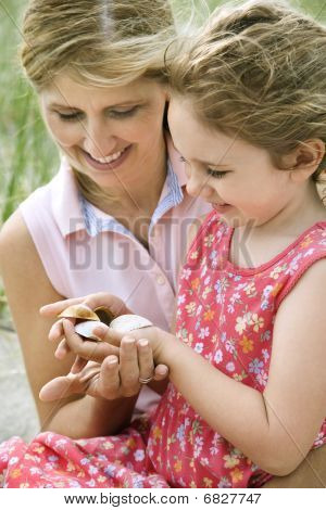 Mother And Daughter Looking At Shells