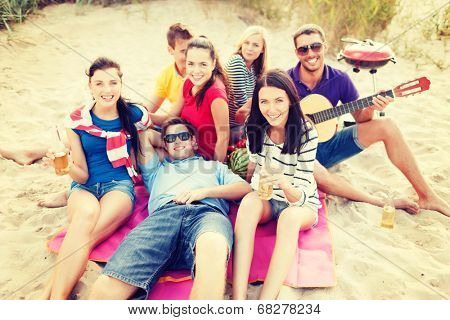 summer holidays, vacation, music, happy people concept - group of friends with guitar having fun on the beach