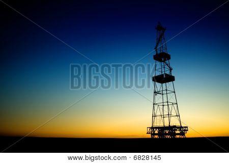 Oil Rig Silhouette Over Blue Sky