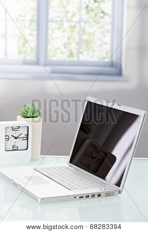 Laptop photo with blank screen on top of table.