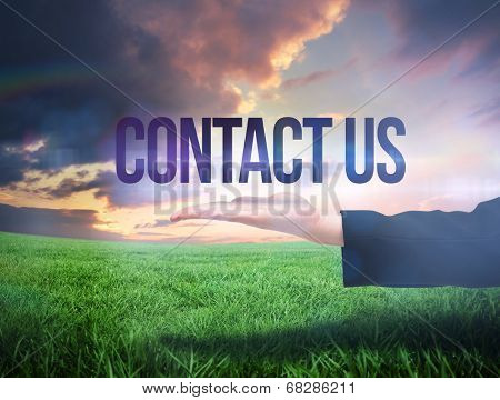 Businesswomans hand presenting the word contact us against green field under orange sky