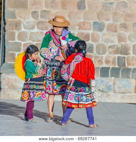 CUZCO, PERU, MAY 1, 2014 - Woman and two girls in regional attire. She is carrying a llama baby and earn money posing for tourists.