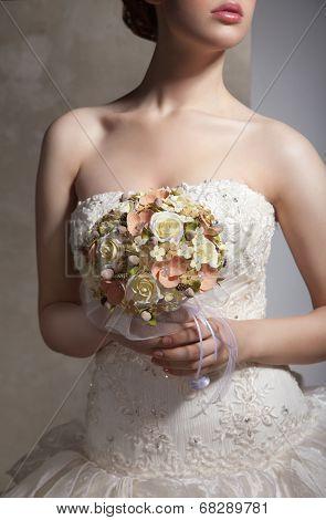 Bride is holing wedding flowers. Focus on flowers