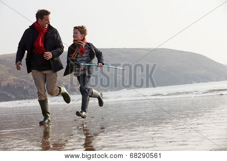 Father And Son Running On Winter Beach With Fishing Net