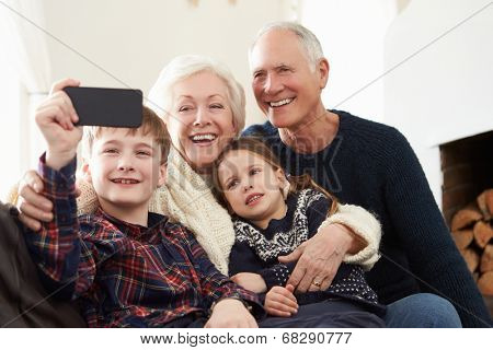 Grandparents And Grandchildren Sitting On Sofa Taking Selfie