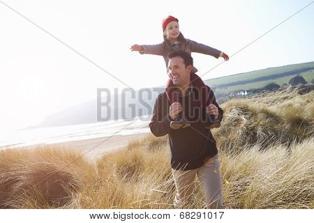 Father And Daughter Walking Through Dunes On Winter Beach