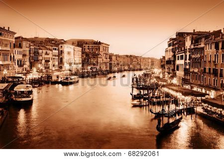 Venice, Italy. Gondola floats on Grand Canal, Italian Canal Grande at sunset. View from Rialto Bridge. Vintage style, monochrome gold.