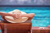foto of beach hat  - Luxury female tanning on the beach - JPG
