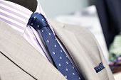 image of coat tie  - Closeup of the upper section of a grey man suit with striped shirt grey coat and blue spotted tie in a store or showroom - JPG