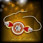 image of rakhi  - Beautiful rakhi on shiny brown background for Happy Raksha Bandhan celebrations - JPG