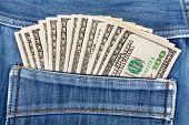 picture of denim jeans  - A hundred dollar bills sticking in the back pocket of denim blue jeans - JPG