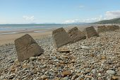 pic of bollard  - Pebbles and concrete bollards make up the sea defences on the beautifull Fairbourne beach Gwynedd Wales UK