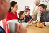 stock photo of grandparent child  - Multi Generation Family Eating Lunch At Kitchen Table - JPG