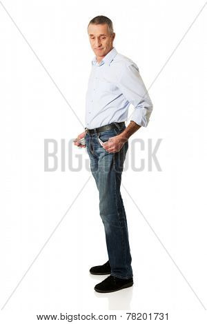 Full length confused man showing his empty pockets.