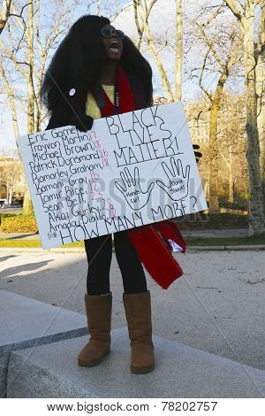 A protester holds a sign against police brutality and grand jury decision on Eric Garner case