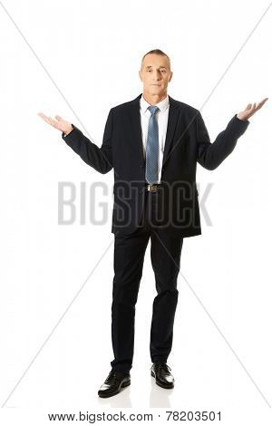 Full length businessman in undecided gesture.