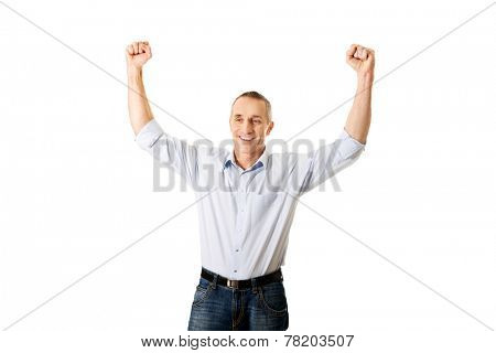 Portrait of a winner mature man with arms up.
