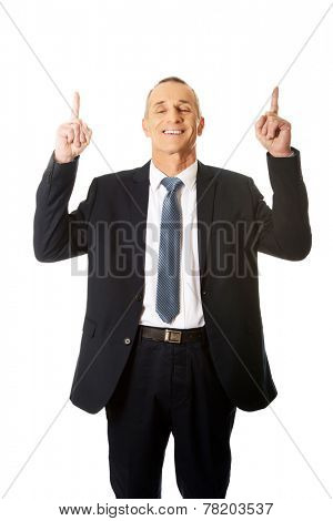 Businessman pointing upwards and smiling at camera.