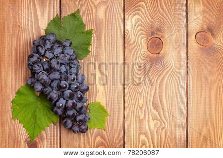 Bunch of red grapes on wooden table background with copy space