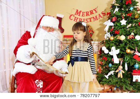 Little cute girl giving letter with wishes to Santa Claus near Christmas tree at home