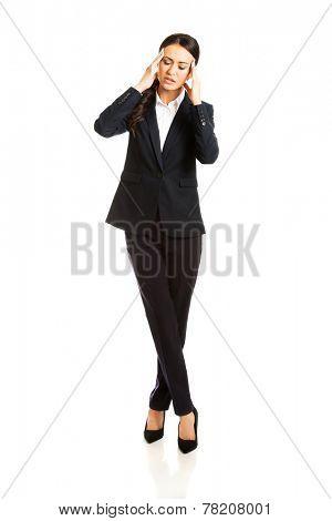 Full length businesswoman having huge headache.