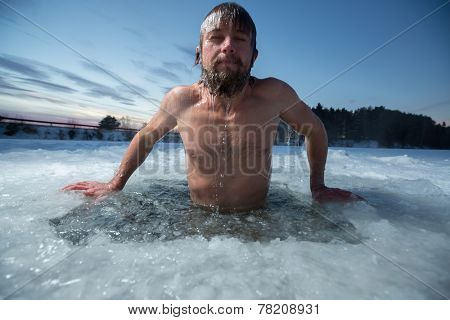 Young man bathing in the ice hole