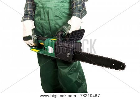 Gardener in green uniform and gloves holding chainsaw.