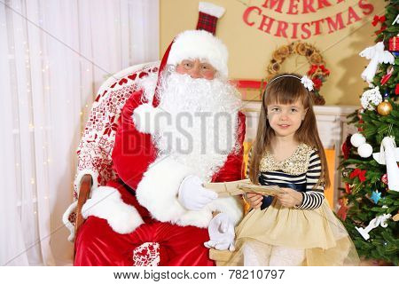 Little cute girl giving letters with wishes to Santa Claus near Christmas tree at home