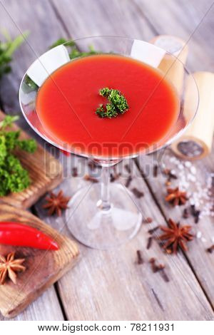 Tomato juice in goblet and fresh vegetables on cutting board on wooden background