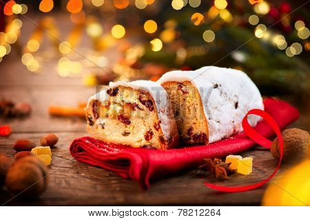 Christmas Stollen. Traditional Sweet Fruit Loaf with Icing Sugar. Xmas holiday table setting, decorated with garlands, baubles, wallnuts, hazelnuts, cinnamon sticks. Warm colors toned. Vintage styled
