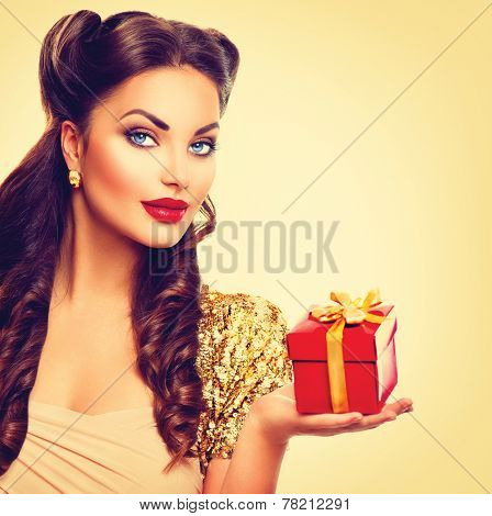 Beauty Pin up girl with holiday gift box in her hand. Retro woman portrait. Vintage styled make up and hairstyle. Pinup style lady