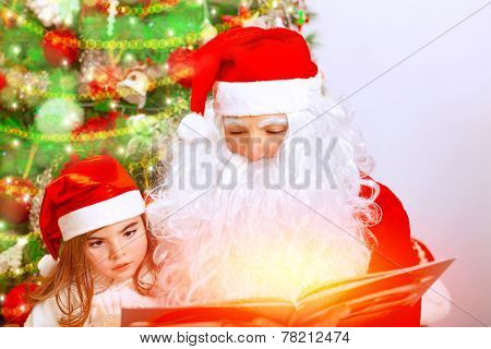 Portrait of Santa Claus with cute granddaughter sitting near Christmas tree, studio shot, reading magic book, celebrating winter holidays