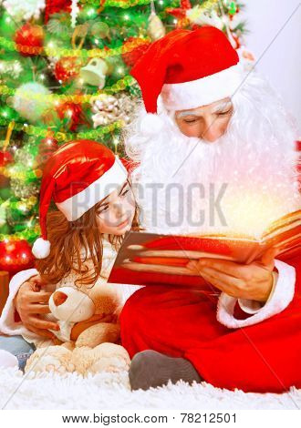 Happy Christmas eve at home, cute little girl sitting near beautiful xmas tree and reading magic book with Santa Claus, enjoying winter holidays concept