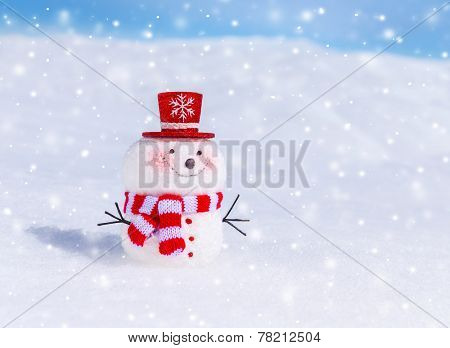 Cute snowman outdoors in snowy weather, traditional winter symbol, little smiling snowman wearing red hat and scarf, Christmas greeting card