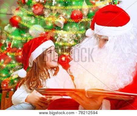 Closeup portrait of adorable baby girl with Santa Claus sitting near beautiful Christmas tree background and reading magical winter fairytale, happy childhood concept