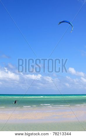 Man involved in kiteboarding on the coast of Cuba.