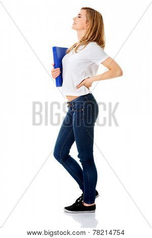 Side view of woman with back pain holding a binder.